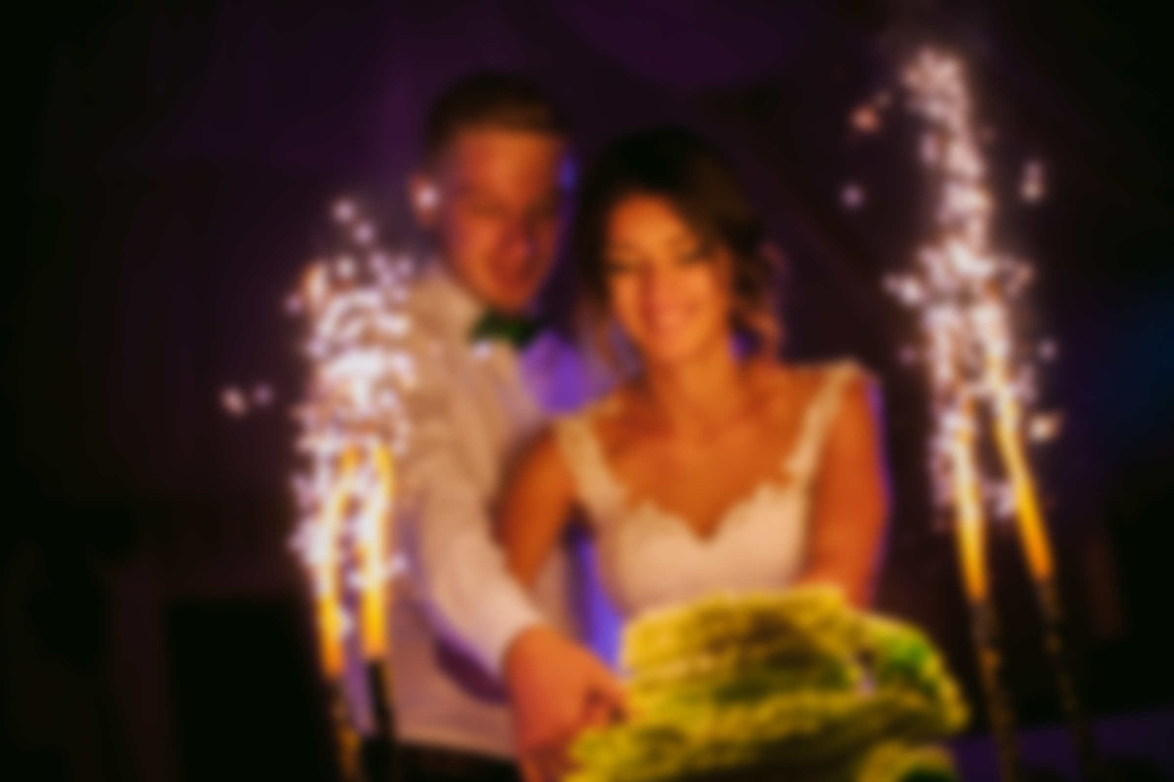 Blurred photo of a bride and groom cutting their cake.