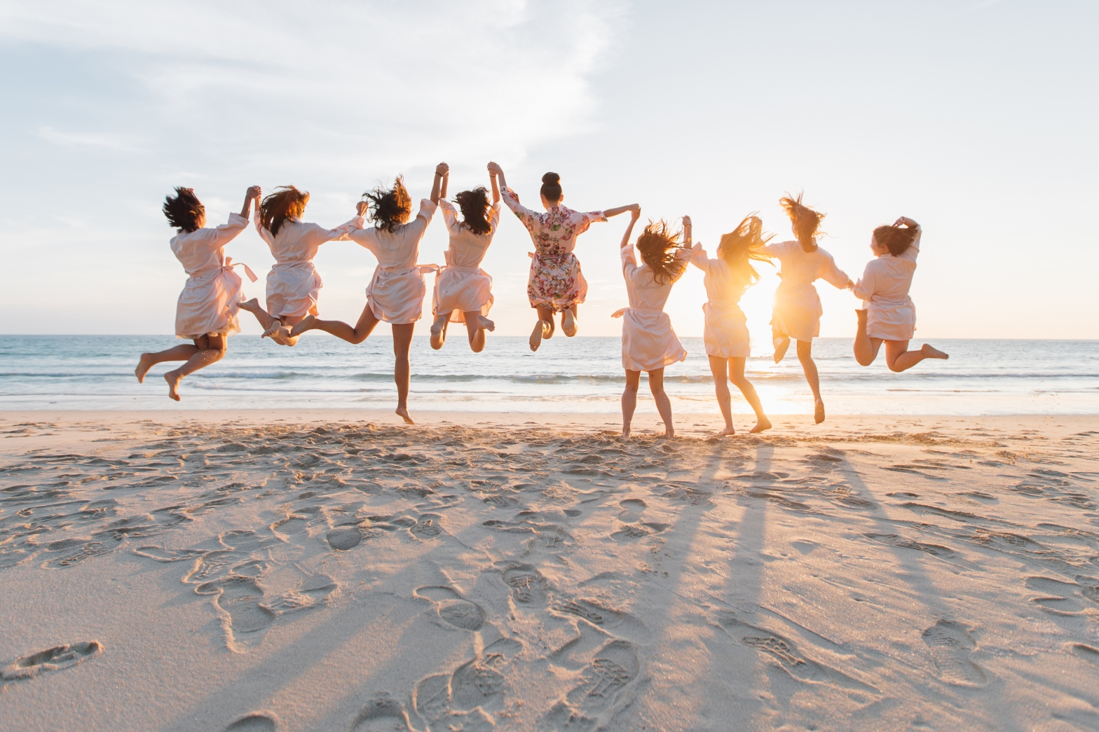 Bridesmaids jumping on the beach in their dressing gowns