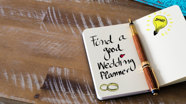 "Note book with ""find a good wedding planner"" written inside"