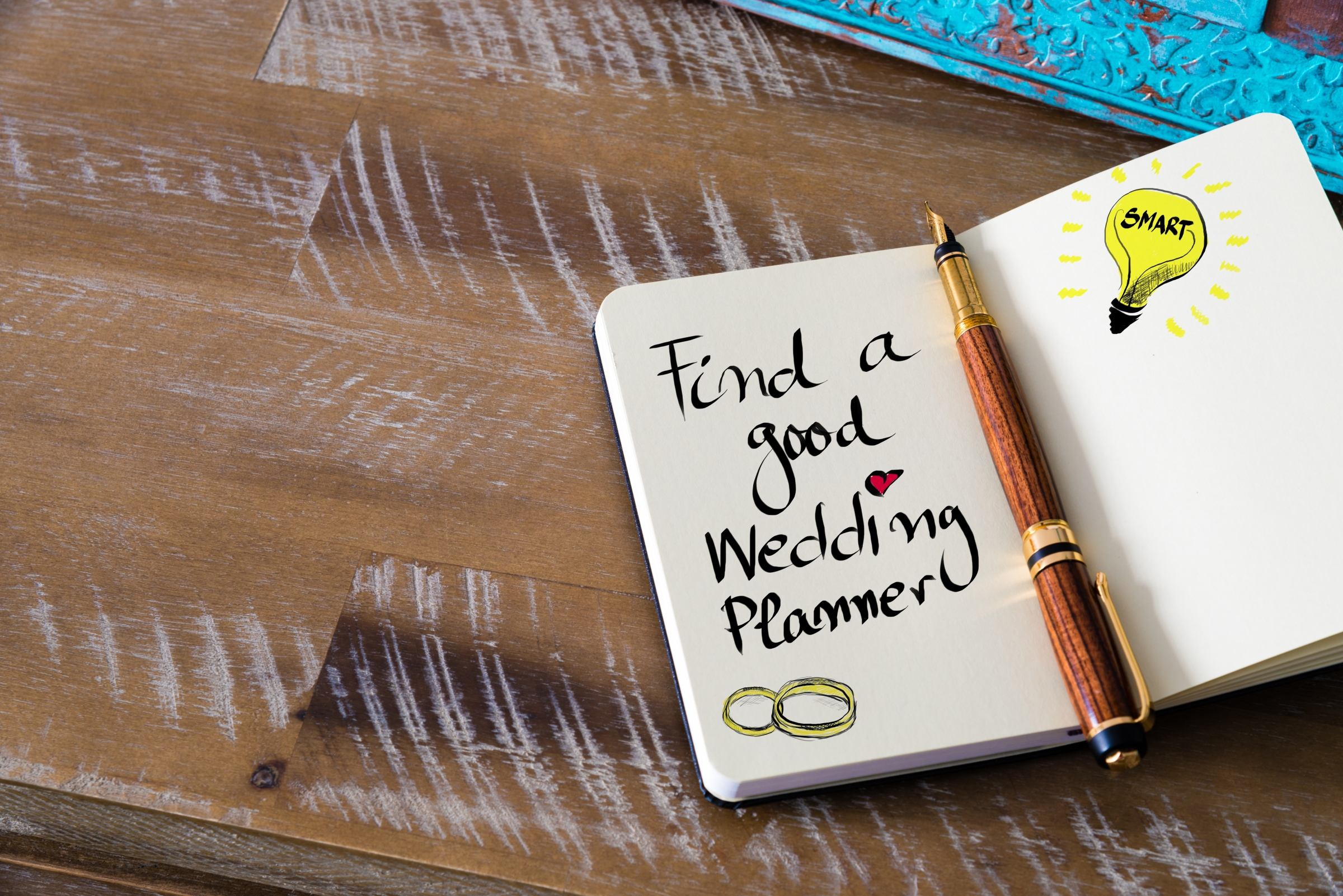 "Note book with note saying ""find a good wedding planner"""